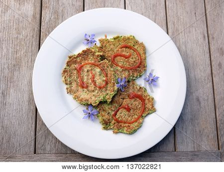 An easy lunch at home of zucchini or courgette fritters with tomato ketchup sauce and edible blue borage flowers on a timber outdoor table.