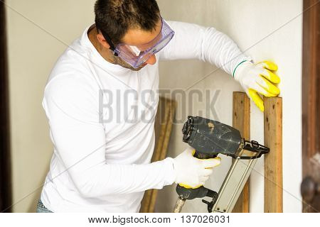 Man doing home repairs with electric stapler