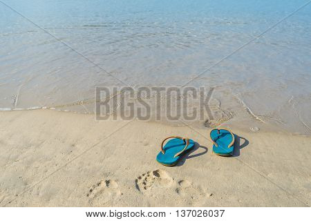Green slippers with the sand beach in Phuket Thailand