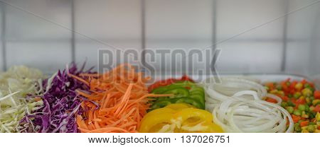 Salad bar with various fresh vegetables on counter