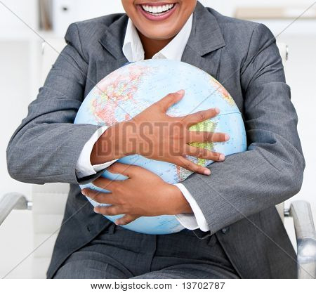 Close-up of a smiling businesswoman holding a terrestrial globe in the office