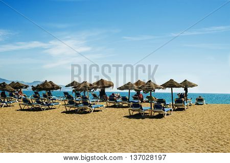 View on sunny idyllic beach with umbrellas and deckchairs against of seascape under blue sky. Malaga Spain Beach La Malagueta.