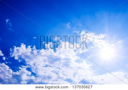Idyllic clear blue sky with fluffy clouds and sunbeams. Beautiful cloudy blue sky background