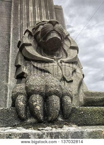 A large concrete lion with huge claws guards the entrance to the Lion's Gate suspension bridge in Vancourver BC