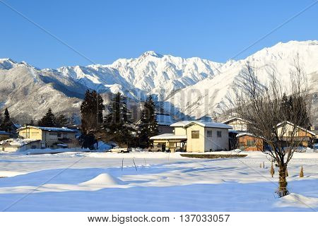 Alpine landscape of snow covered village and mountains on Honshu, Japan.  Villagers farm on the flat land at the base of the mountain range in the warmer months of the year.