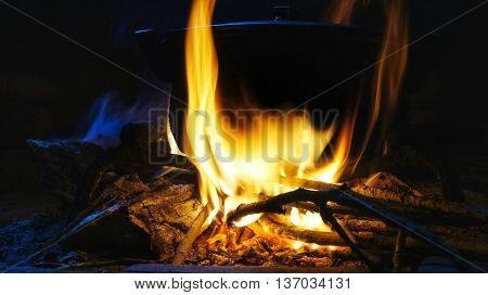 Burning fire with hot pot. Hot food preparation above burning wood pieces.