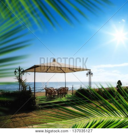 outdoor bamboo sitting set under tent next to beach