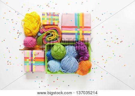 Balls of colored yarn. View from above. All the colors of the rainbow. Sample knit. Crochet. Gifts wrapped in colored paper. Holiday packages show.