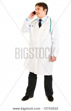 Smiling medical doctor talking on mobile phone isolated on white