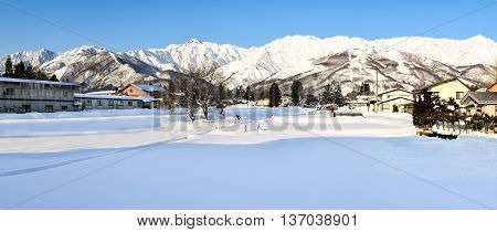 Panoramic alpine landscape of snow covered village and mountains on Honshu, Japan.