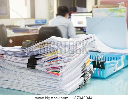 Pile Of Unfinished Paperwork On Office Desk