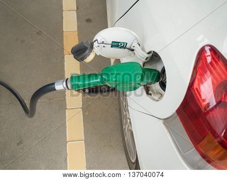 Dirty White Car Refueling On A Gas Station.