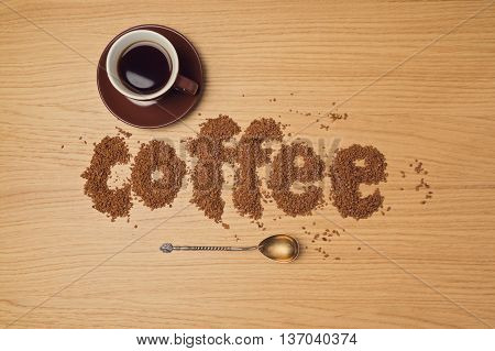 Coffee background with coffee cup and instant coffee letters. View from above