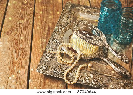 Vintage hand mirror and hairbrush on silver tray over wooden background