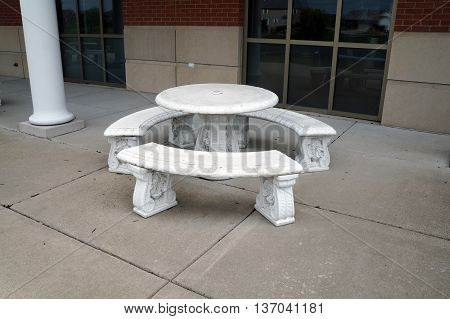 One may sit at a round white table outside the Village of Shorewood Village Hall in Shorewood, Illinois.