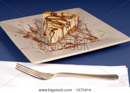 A Piece Of Cheesecake With Chocolate Drizzled Over It With Fork
