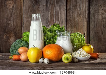 Set of different foods on the old wooden background vegetables fruit eggs dairy products the concept of a balanced diet vegetarian food