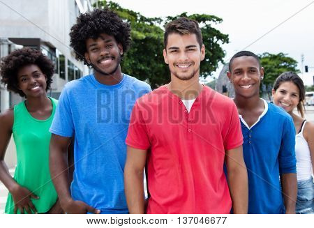 Group of hip and cool young adults laughing at camera in city in the summer