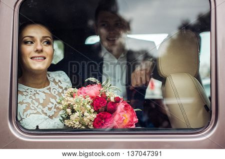 Bride and groom looking SUV through the car window into the future, the view through the glass of the car