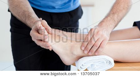 Close-up of a Caucasian physical therapist giving a foot massage in a health center