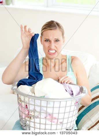 Disgusted woman doing her laundry at home