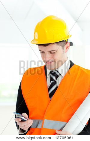 Portrait of a smiling male architect holding a phone