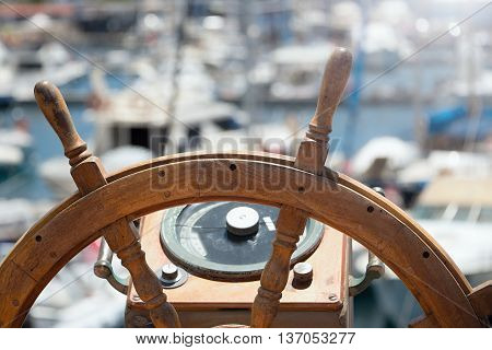 Captains steering wheel of an old wooden sailing ship in a port