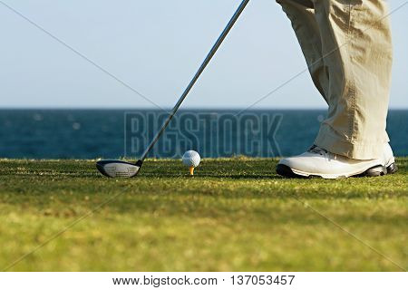 Golfer is going to tee off at sunset, ocean and horizon