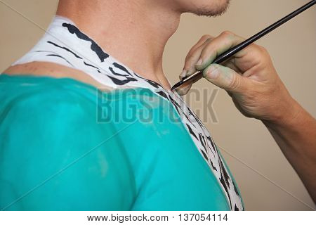 Body painting in process.Young male nude body art painter