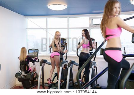 At fitness centre. Image of girls practicing on simulators