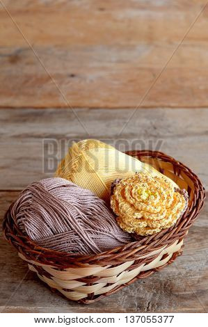 Crocheted yellow rose with brown leaves and two skeins of cotton yarn in a basket. Beautiful knitted flower adorned with beads. Stylish crochet crafts. Old wooden background with empty space for text