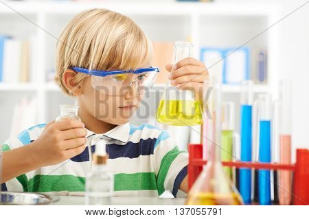 Boy in goggles holding flask with chemical reagent
