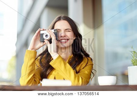 travel, tourism, photography, leisure and people concept - happy young tourist woman or teenage girl with film camera and guidebook drinking cocoa at city street cafe terrace