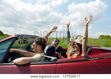 leisure, road trip, travel and people concept - happy friends driving in cabriolet car at country and having fun