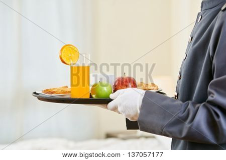 Room service bringing healthy breakfast with orange juice and fruits