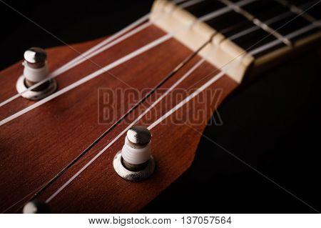 a ukulele on black background. Close up