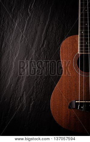 a ukulele on black background. Top view