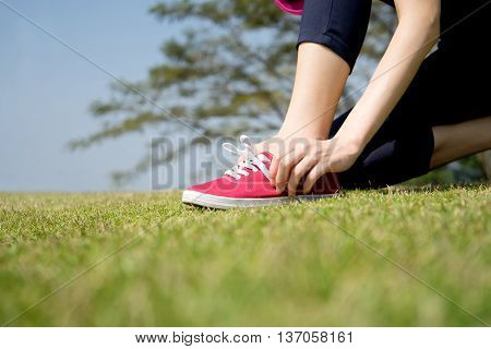 Running shoes - closeup of woman tying shoe laces on her barefoot running shoes. Female sport fitness runner getting ready for jogging outdoors.