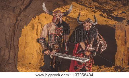 Couple Of Vikings In Armor With Swords. Catacombs On The Background.