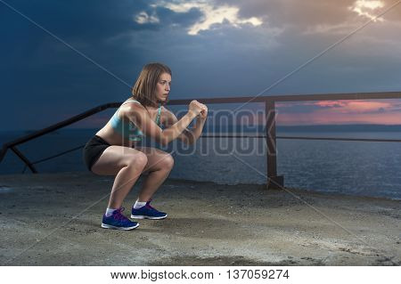 Fit caucasian woman in sportswear doing squats on sea pier at sunset. Fitness workout outdoors