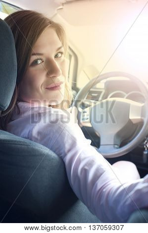 Young caucasian smiling woman in car holding steering wheel