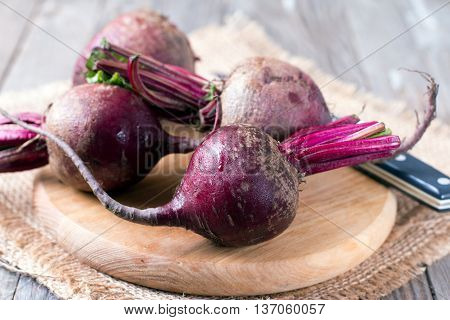 Raw organic red beets on wooden table