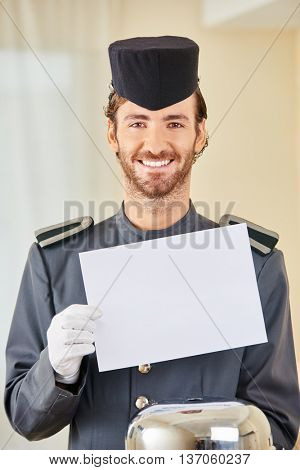 Smiling hotel page with white empty sign and food cloche in hotel room