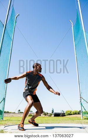 Athlete abiut to throw discus in the stadium