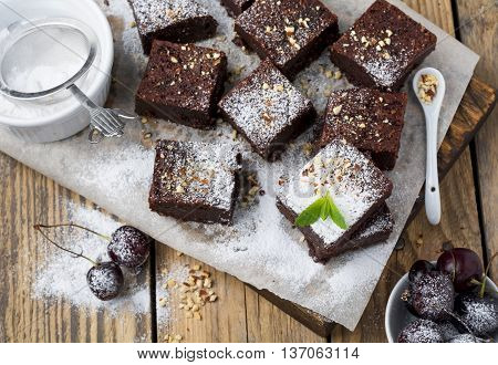 Chocolate brownies with powdered sugar and cherries on a dark wooden background. Selective focus.