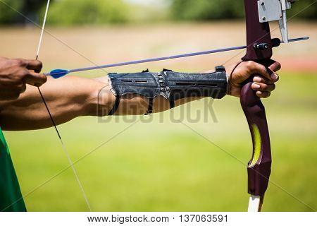 Athletes hand practicing archery in stadium