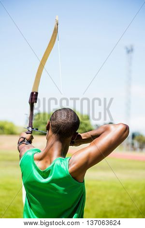 Rear view athlete practicing archery in stadium