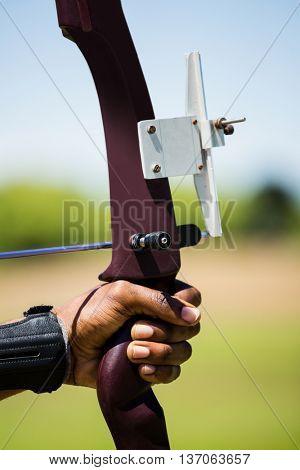 Close-up of athlete hand practicing archery in stadium