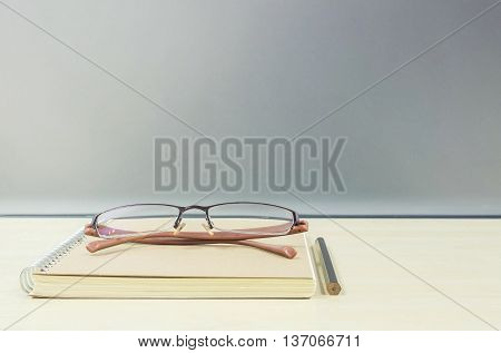 Closeup brown note book on blurred wooden desk and frosted glass wall textured background work concept by brown note book eyeglasses and pencil