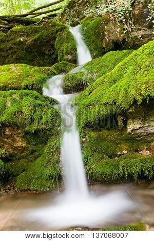 Small waterfall on mountain brook among green stones